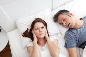 Woman covering her ear next to snoring man.
