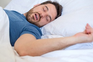 Man in blue shirt snoring loudly in bed