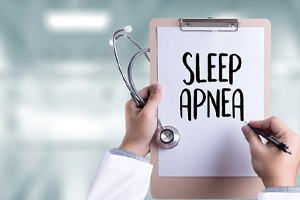 "Doctor's hands holding clipboard with ""sleep apnea"" written on it"