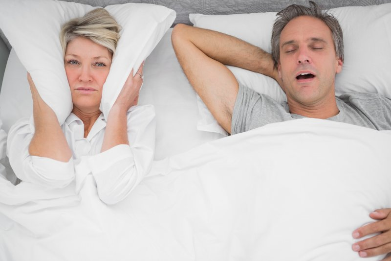 a woman with a pillow over her ears while her husband snores