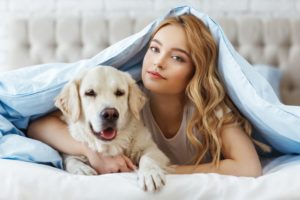 girl in bed with golden retriever
