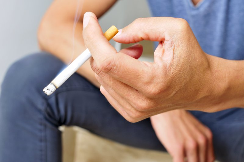 male hand holding lit cigarette