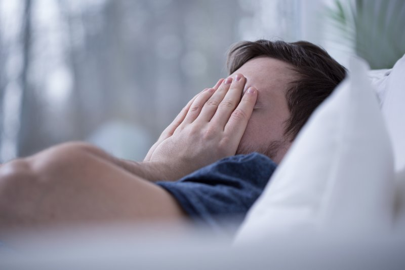 Man lying in bed awake and covering his face