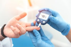 medical professional testing a patient's blood sugar