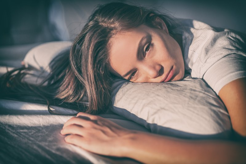 Depressed woman laying face down on pillow
