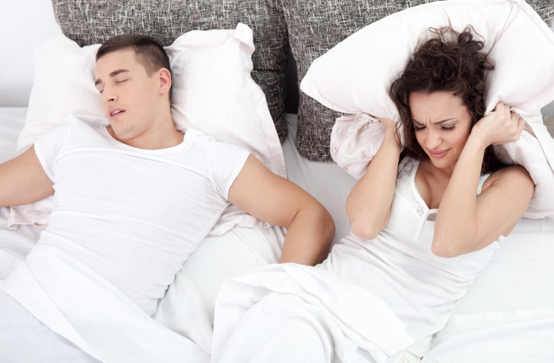 a man sleeping with his mouth open and a woman holding a pillow over her ears because of his snoring